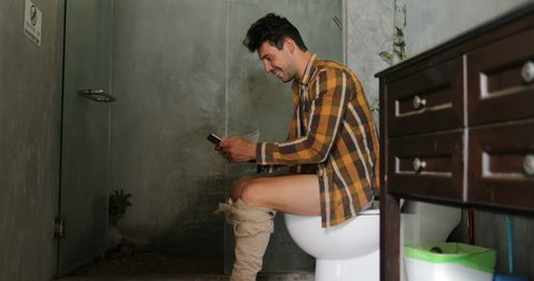 Man Sitting On Toilet Use Cell Smart Phone Young Guy Chatting Online In Restroom