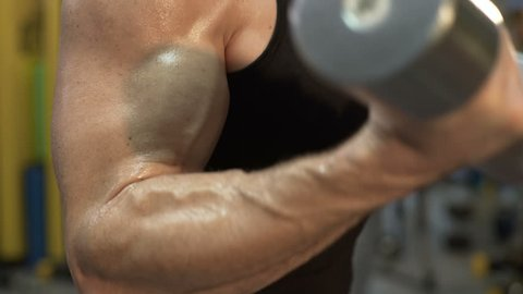 Guy flexing arms with dumbbells in his hands, gym workout, hunky body closeup
