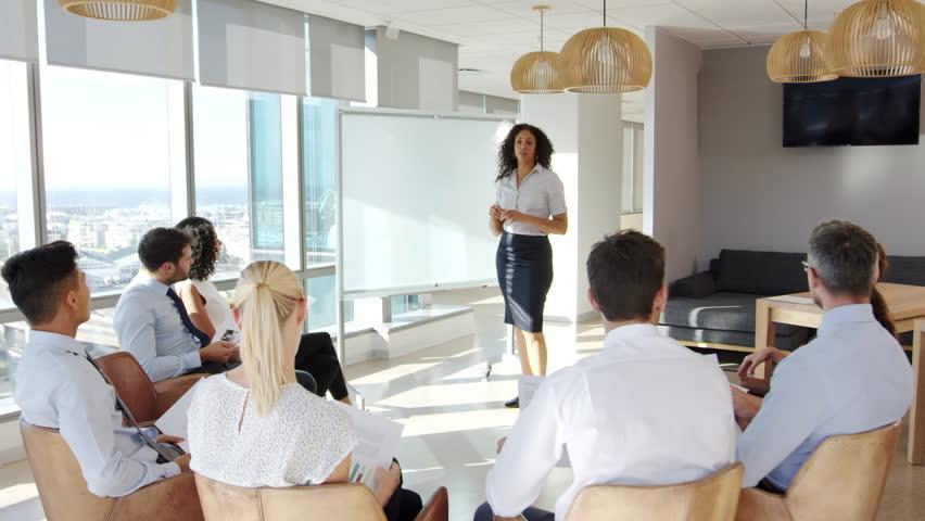 Businesswoman Making Presentation Shot Through Doorway   Shutterstock HD Video #26817436