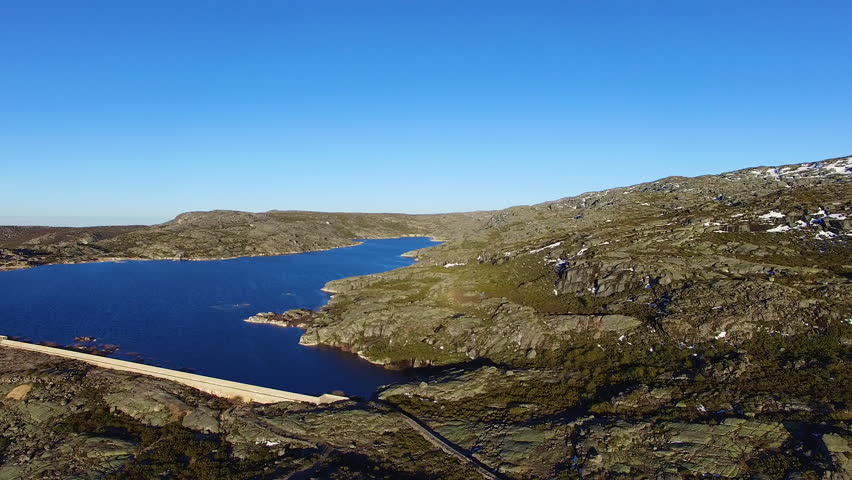 Aerial of a dam, flying an arc and revealing the whole lake, little white House on the peak of some rocks, located in Serra da Estrella, Portugal, beautiful blue water and cloudless sky, 4K Drone