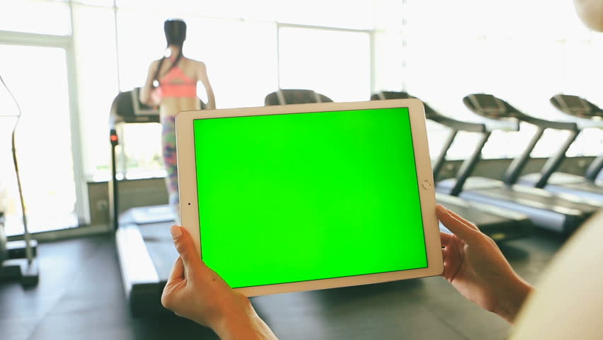 Hands holding tablet computer with green chroma key screen. On the background sport club with Treadmills and woman having running workout. video footage    Shutterstock HD Video #26834716