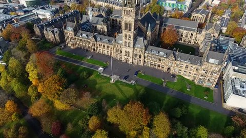Flying in Autumn over the Kelvingrove park in Glasgow, Scotland towards the Gilbert Scott tower at Glasgow University.