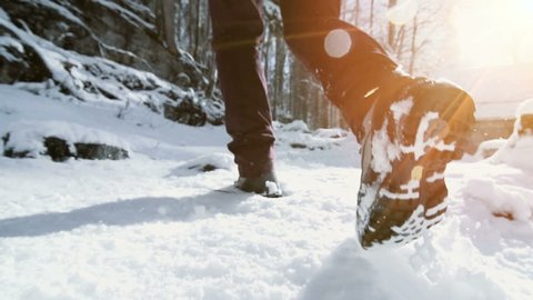 feet walking in deep snow shot in slow motion. foot steps of hiker. recreational winter activity outdoors