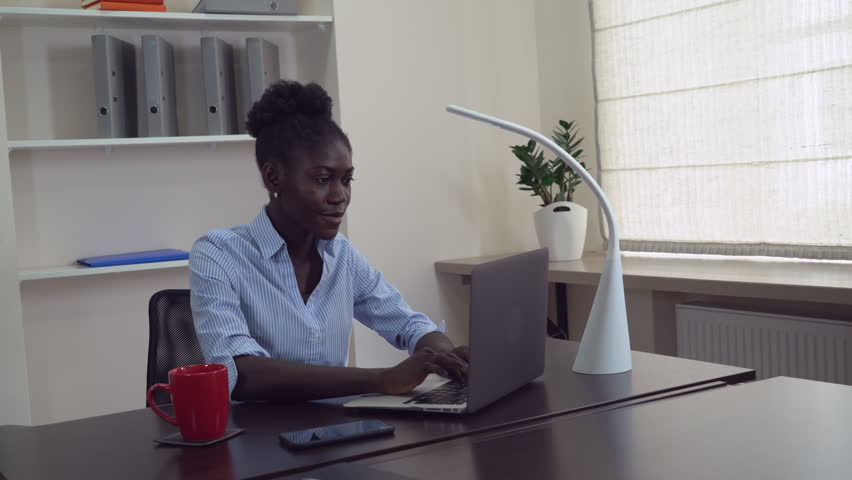 Afro american businesswoman working in office. Young professional woman sitting at the working place typing on computer. Happy manager chatting online or entering data on laptop. | Shutterstock HD Video #26850556