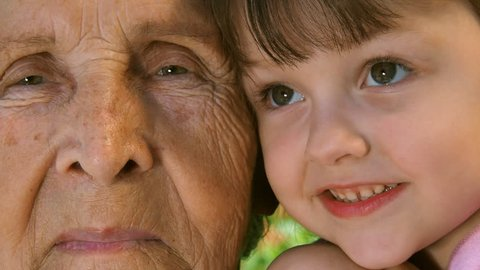 Grandmother with granddaughter. Portrait of an elderly woman and a child. The face of an elderly woman and a child. Grandmother with grandson close-up. Elderly and younger eyes. Two faces close-up.