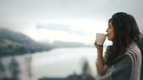 The close-up view of the woman wrapped in the plaid and drinking tea at the background of the river and meadow.