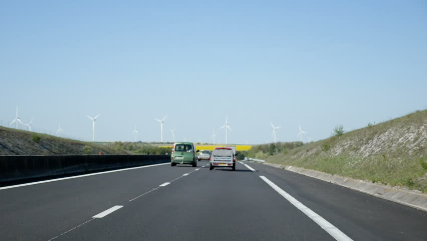 Defocused point of view of driver looking at the busy jam French autoroute with electrical wind mill power plant in the perspective