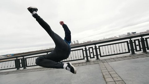 Slow-motion Acrobatics - teenager performing somersault outdoor