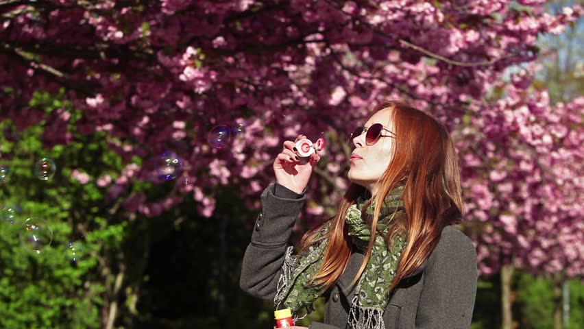Young girl blows a bubbles in a sakura garden. Looping movie. Cinemagraph. | Shutterstock HD Video #26889946