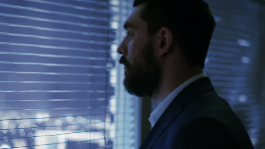 Late at Night Businessman Looks Through Window Blinds and Looks on Big City with Skyscrapers.  | Shutterstock HD Video #26897086