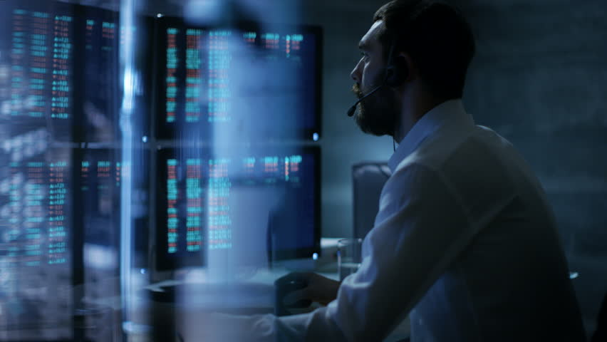 Late at Night Trader Reads Numbers on His Multiple Displays with Stock Information on Them, He Also Consults Clients with Headset On. In Background Big City Window View. Shot on RED EPIC-W 8K Helium. | Shutterstock HD Video #26897116