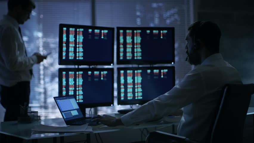 Late at Night in Trader's Bureau. Stockbroker Reads Numbers on His Multiple Displays with Stock Information on Them,He Also Consults Clients with Headset On.