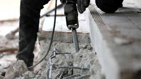 Worker using concrete drilling machine to break the hard floor, video taken with slow motion technique