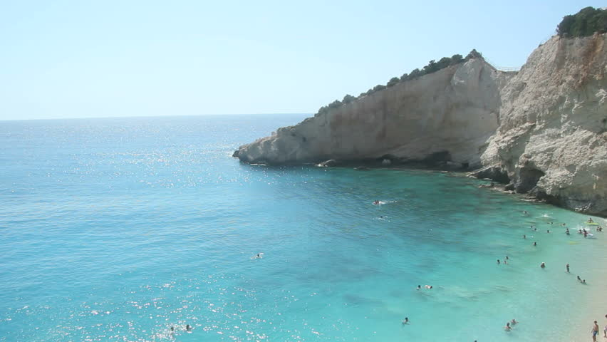 Blue Sea - Porto Katsiki, Lefkada - Crystal clear shallow blue water of Ionian sea, unrecognizeable people swimming in the distance, Greek Island of Lefkas, Lefkada, Greece