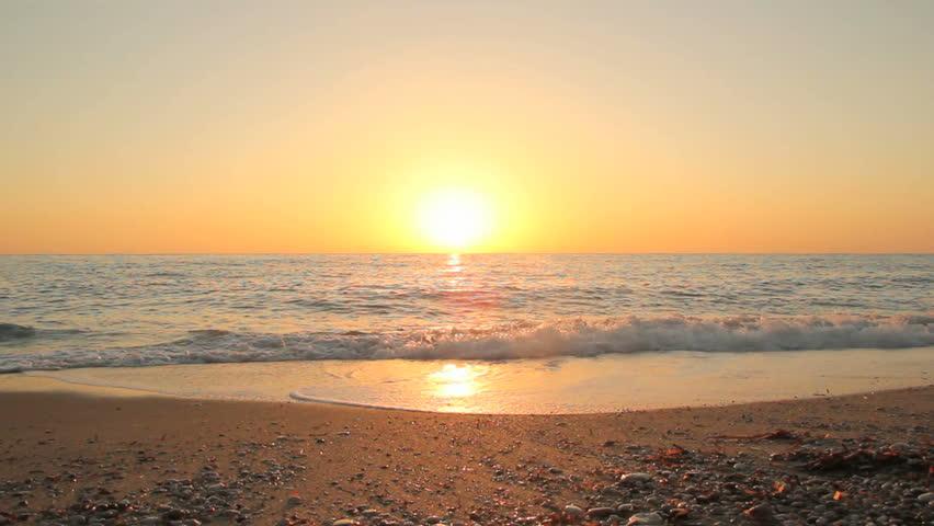Sunset on the beach - Tranquil idyllic scene of a golden sunset over the sea, waves slowly splashing on the sand #2691179