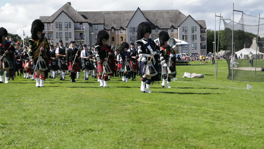 NAIRN, SCOTLAND - AUGUST 18: Massed pipe bands marching at the Highland Games in Nairn, Scotland on August 18, 2012. Highland games events are a popular tourist attraction during the Scottish summer.