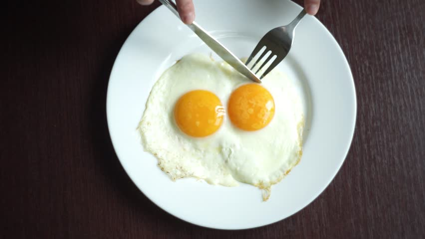 Fried eggs eating. Top view of fried eggs eating with fork and knife. Traditional breakfast eggs eating. Morning breakfast service
