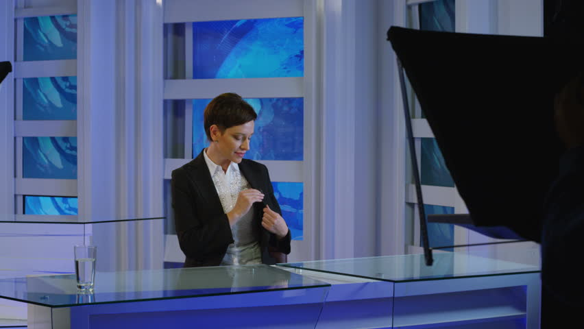 News reporter talking in studio.  News reporter finishing work in studio and putting down microphone .  | Shutterstock HD Video #27003016
