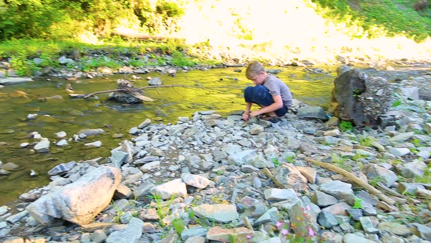 Portrait of cute funny little kid cheerfully splashing water in mountain landscape outside. Handsome white 9 year old boy having fun with family on summer day during holiday travel. Real time footage. #27023377