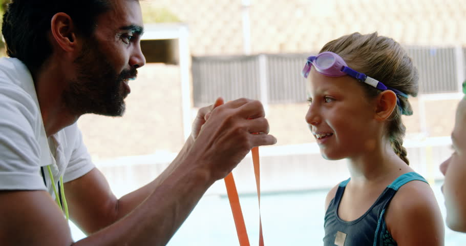 Male trainer giving gold medal to his student near poolside.