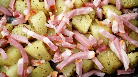 Peeled potatoes with spices, bacon meat and onion slices ready to be roasted close up. Food background. Dolly shot