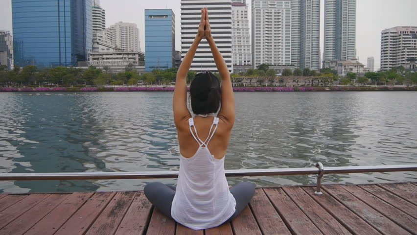Asian slim woman practice yoga lotus pose (Padmasana) in park, urban city building background HD 1920 x 1080 | Shutterstock HD Video #27098386