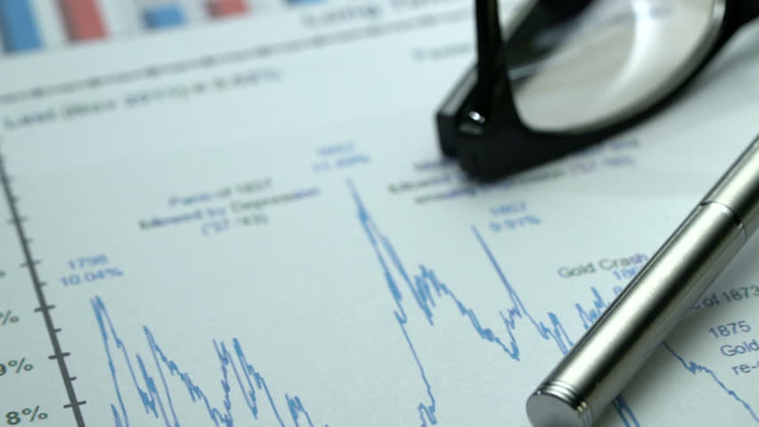 Tracking macro shot of office desk with business graphics, glasses, pen and notebook. | Shutterstock HD Video #27124225