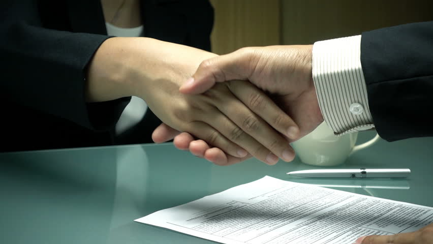 Slow motion of two businesspeople shaking hands each other after signing a contract in the office.