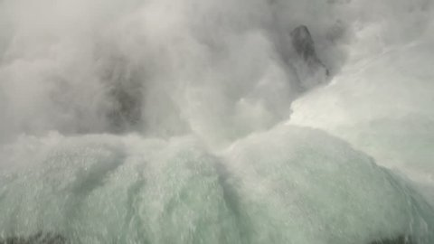 AERIAL TOP DOWN CLOSE UP: Flying above the raging whitewater river dropping over the steep cliff of Niagara Falls crashing on the rocky bottom. Misty Horseshoe Falls overlooking the Canadian side