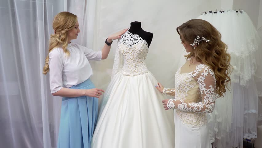 Bride At The Clothes Shop For Wedding Dresses She Is Choosing A Dress And  The Designer