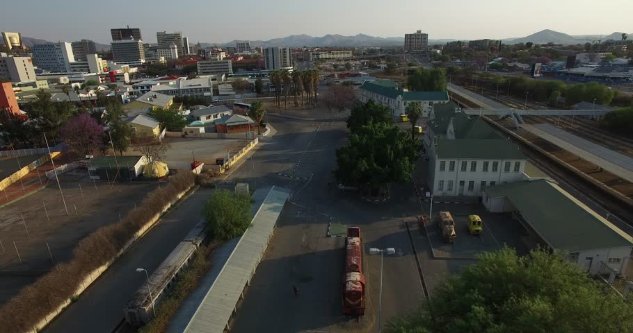 Aerial drone video of capital Windhoek main railway station near Independence Avenue with view of railway tracks, city center skyline in central highland Khomas Hochland of Namibia, southern Africa