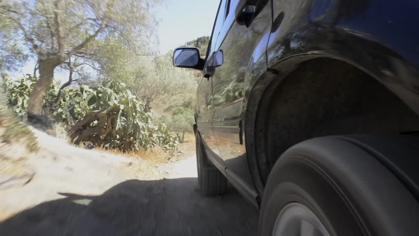 Large four by four drives off road through rugged terrain, seen from behind the rear wheel
