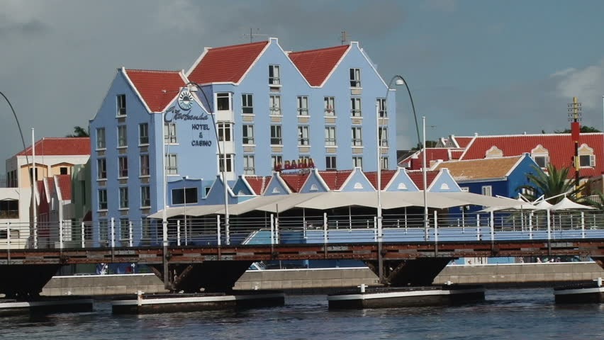 WILLEMSTAD/NETHERLANDS ANTILLES - 11 DECEMBER 2010: The Queen Emma Bridge opening across St Annes Bay in Willemstad, Curacao. A colourful hotel is seen in the background