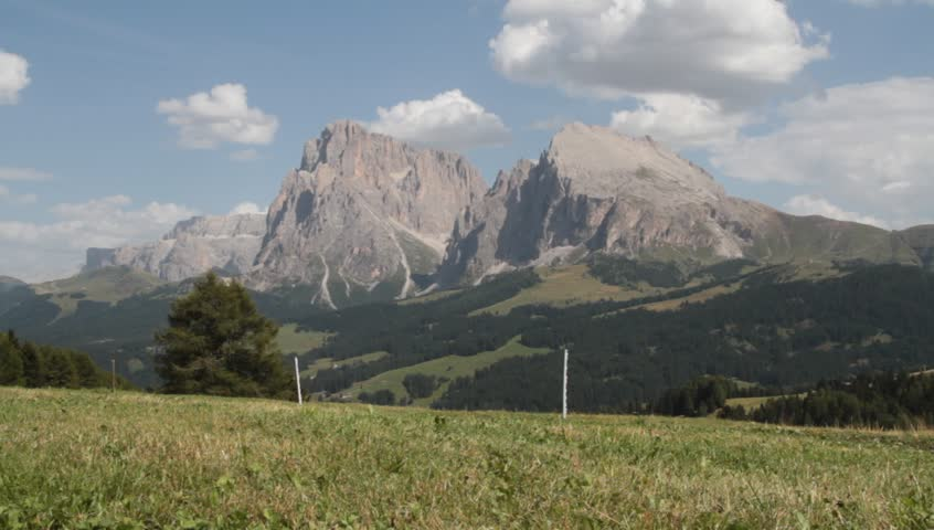 man walks on alpine plateau of siusi (seiser alm) with background dolomites (flat stone and long stone)