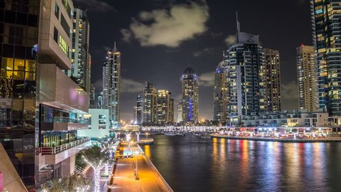 Vew of Dubai Marina promenade with yachts and modern Towers with restaurants from bridge in Dubai night timelapse hyperlapse, United Arab Emirates.