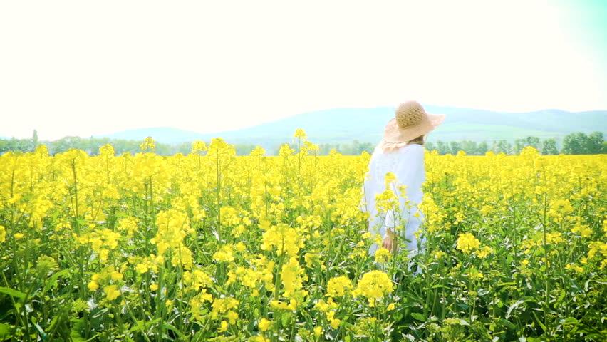 Woman with hat in yellow flowering rape field in summer