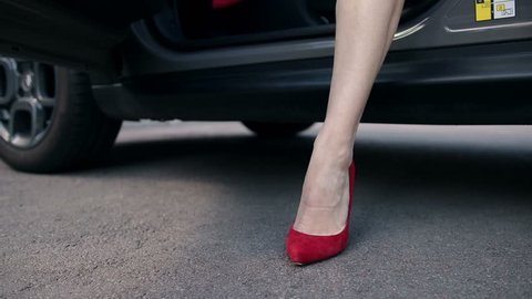 Woman's legs in red high heels stepping out of car