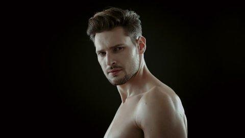 Handsome athlete posing on black background  5k Red Epic slow motion clip