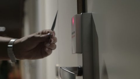 Close-up shot of a hotel guest using card key to open electronic lock of room door