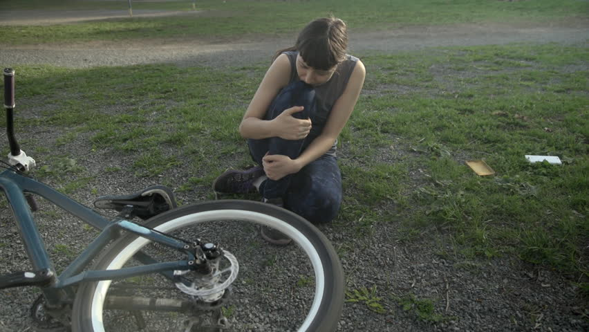 A young woman sits on the side of a dirt road after falling off a bicycle, calms the pain in her bruised leg, next to the phone lies on the grass.