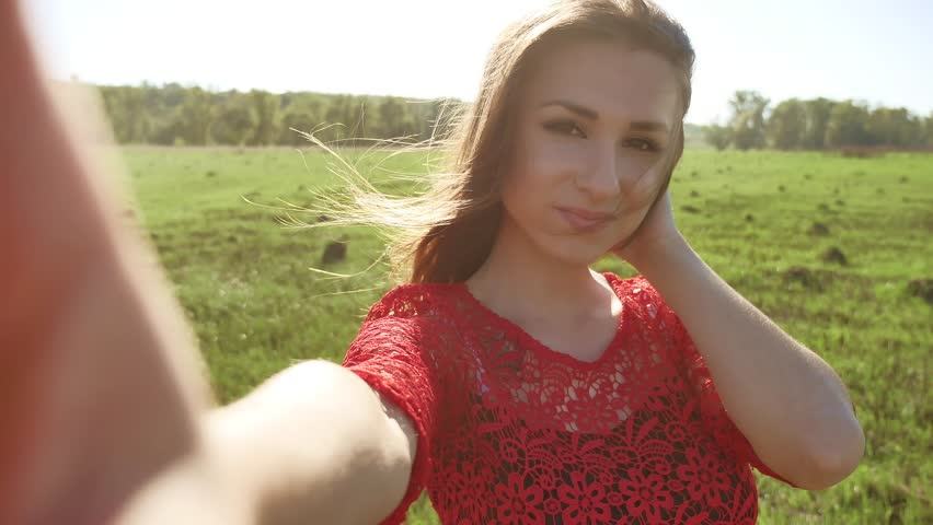 Selfie. The girl makes selfie, takes pictures of herself in nature. Girl hair breeze lifestyle | Shutterstock HD Video #27241441