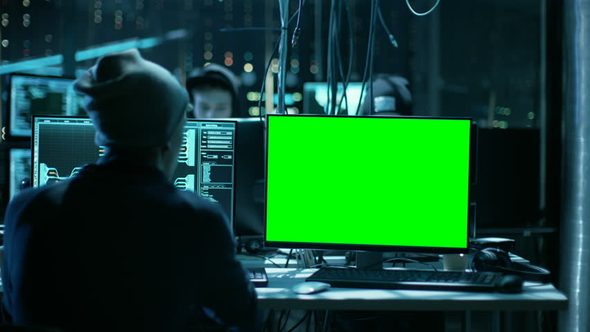 Team of Internationally Wanted Teenage Hackers with Green Screen Mock-up Display Infect Servers and Infrastructure with Ransomware. Their Hideout is Dark, Neon Lit and Has Multiple Displays.    Shutterstock HD Video #27244642