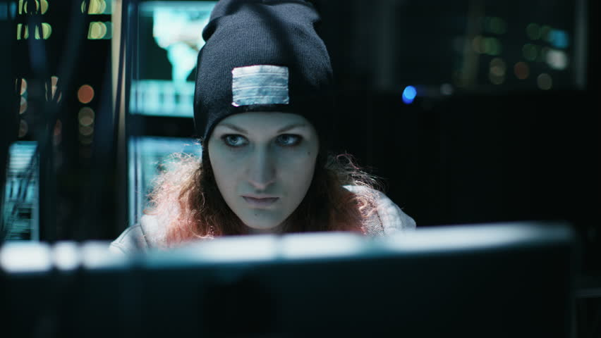 Nonconformist Teenage Hacker Girl with Pink Hair Attacks Corporate Servers with Malware. Room is Dark, Neon and Has Many Displays. Shot on RED EPIC-W 8K Helium Cinema Camera. RED 4K UHD.