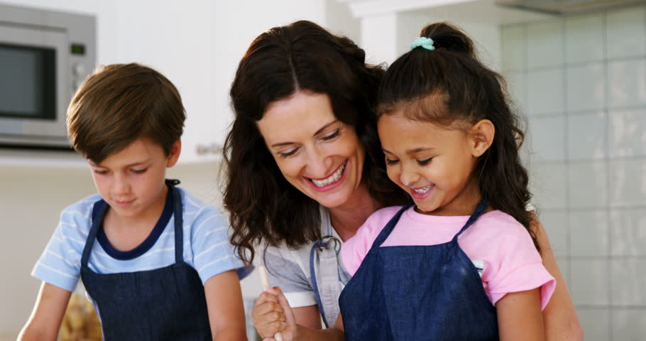 Mother and kids mixing the dough while preparing cookies in kitchen | Shutterstock HD Video #27246706