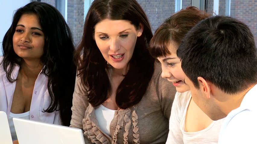 Caucasian and Indian classmates learning with university female lecturer in modern technology room
