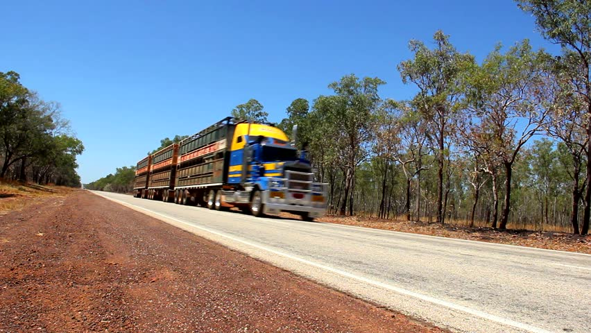 Big truck with three trailers passing by empty road in Outback Australia. Long distance goods transportation concept