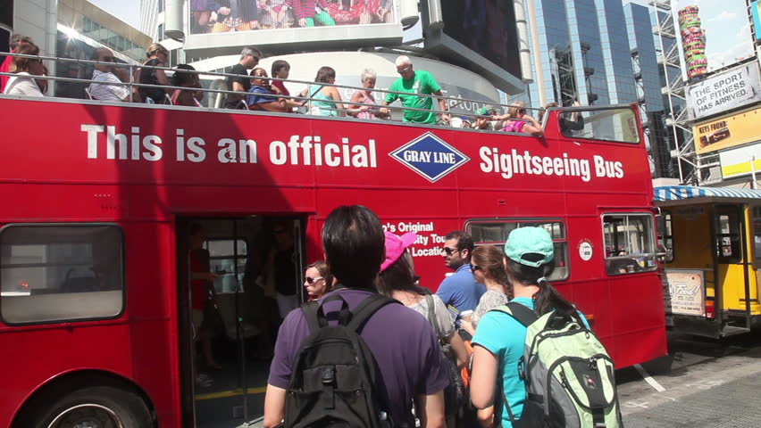 TORONTO, CANADA - AUGUST 14: Tourists boarding a hop on hop off tour bus on Yonge street, Toronto, Canada , august 14th, 2012