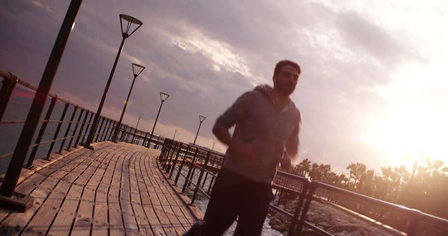 Young male runner with headphones jogging next to a palm tree beach at sunset