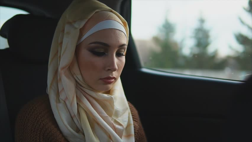 Serious arab woman in a car on a passenger seat. She rides in a car and watching out the window.