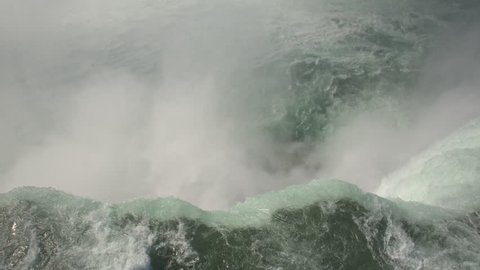 AERIAL CLOSE UP: Flying above the raging whitewater river and over the edge of Niagara falls, tilting down towards the misty bottom. TOP-DOWN aerial view of Horseshoe falls in Niagara river.